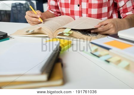 Young Woman And Man Studying For A Test/ An Exam. Tutor Books With Friends. Young Students Campus He