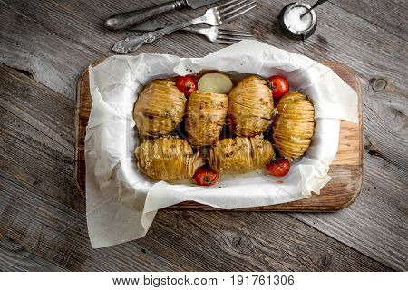 Golden baked potatoes with baked tomatoes in dish, topview, baked in their skin
