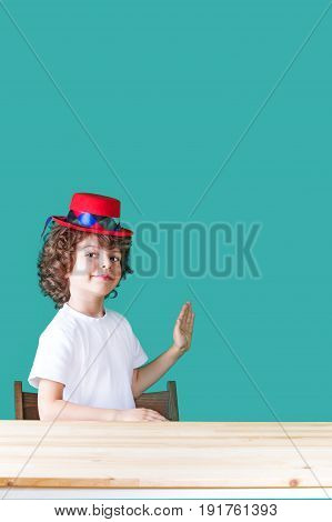 Little Curly Boy In A White Shirt And A Crimson Hat Clown Sitting At A Table Half-turned, Raised His