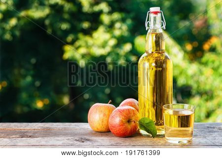 apple cider in glass and in bottle with fresh apples on wooden table with blurred natural background. Copy space. Summer drink