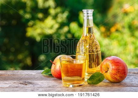 apple cider or juice in glass decanter with ripe fresh apples on wooden table with green natural background. Copy space. Summer drink
