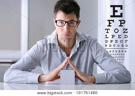 male face with spectacles on eyesight test chart background eye examination ophthalmology concept