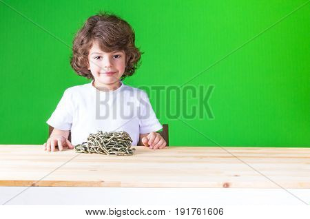 Happy Little Curly-headed Boy In A White Shirt Sits At A Table. On The Table Is A Chain Coiling. Clo