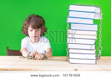 Sad Little Curly-headed Boy In A White Shirt Sits At A Table Chained To Books. Close-up. Green Backg