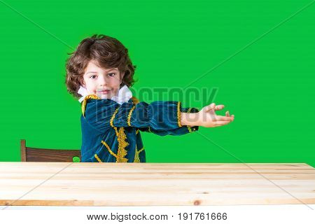 Little Boy In Prince's Dress Sits At A Table Holding Two Hands On An Imaginary Object, Looking At Th
