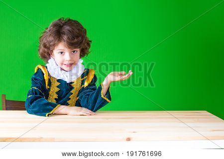Little Boy In A Dress The Prince Sitting At A Table Holding In His Left Hand An Imaginary Thing, Loo