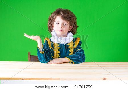 Cute Little Prince Sitting At A Table On The Right Hand Holding An Imaginary Object, Looking At The