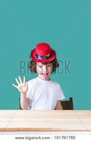 Little curly boy in a white t-shirt and a crimson hat clown sitting at the table his tongue hanging out showing an open hand and looking into the camera. Close-up. Blue background.