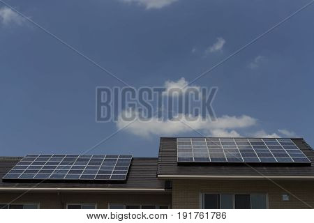 Solar panels on roof of a house with blue sky background