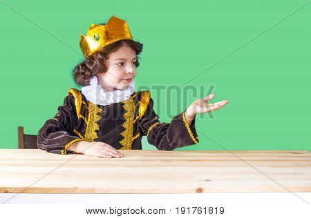 Little Cute King In The Crown Holds An Imaginary Object. Close-up. Green Background.