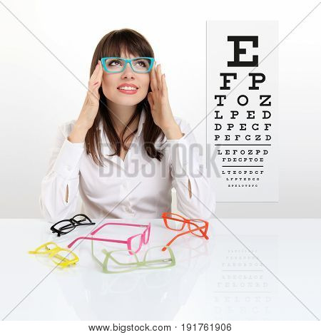 smile female face chooses spectacles on eyesight test chart background eye examination ophthalmology concept
