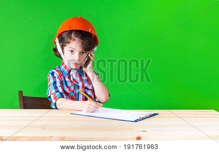 Young Handsome Foreman In Helmet Writing In Pencil In A Notebook Looking At The Camera. Close-up. Gr
