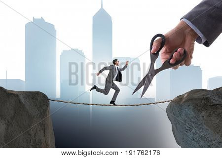 Hand cutting the rope under businessman tightrope walker