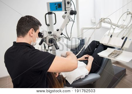 Male Dentist With Dental Tools - Microscope, Mirror And Probe Treating Patient Teeth At Dental Clini