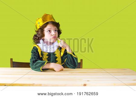 Little Curly King Sternly Looking Up. Green Suit. Yellow Background.