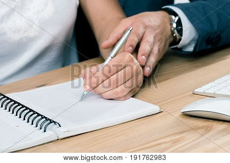 Cropped Shot Of Businessman Touching Hand Of Young Businesswoman Writing In Notebook