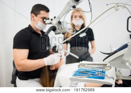 Male Dentist And Female Assistant Treating Patient Teeth With Microscope At Dental Clinic Office. Fo
