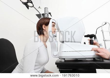 woman doing eyesight measurement with optician slit lamp