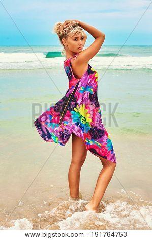 Young beautiful blonde woman posing in sea scenery