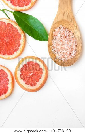 Ayurveda face skin scrub ingredients pink Himalayan salt in wooden spoon sliced grapefruit green leaf on white background beauty health wellness copyspace