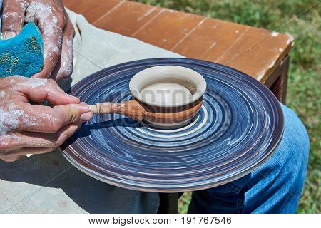 On the potter's wheel revolve a spinning of a clay cup. Potter puts a paint on the cup