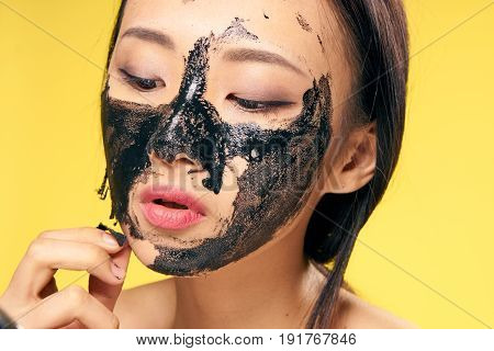 Woman takes off cosmetic mask, woman in cosmetic mask on yellow background portrait.