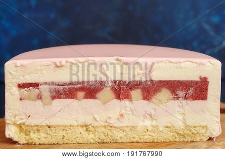 Cut of strawberry cake with pink glaze closeup