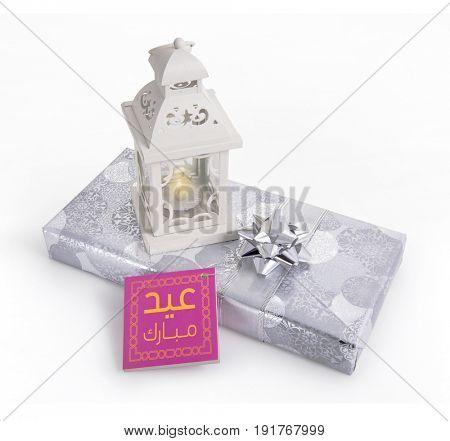 Modern ramadan lamp with a gift having tag with 'Eid Mubarak' message in arabic script.