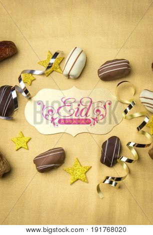 'Eid Mubarak' message in English written on golden plaque surrounded with exotic date chocolates and confetti.Beautiful Eid celebration background.