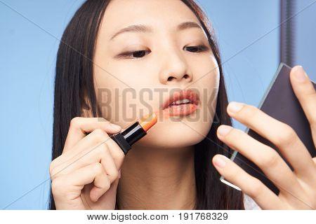 Woman paints lips, woman looks in mirror, woman smears lipstick on face on blue background portrait.