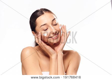 Woman applying cream on face, woman with cream on face, face treatment, facial treatment with cream on isolated background.