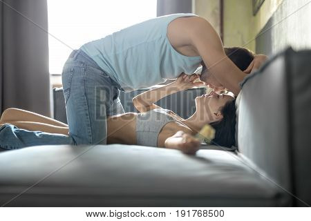 Delightful girl lies on the sofa and holds a flower in left hand. Her boyfriend stands on the knees over her body and prepares to kiss her while she touches her chin. Indoors. Horizontal.