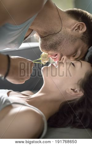 Handsome guy prepares to kiss his girlfriend who lies under him with closed eyes. He wears a light sleeveless and holds a flower in the hand. Girl wears a gray top. Closeup. Indoors. Vertical.