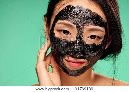 Face care, skin problems, woman in a cosmetic mask on a green background.