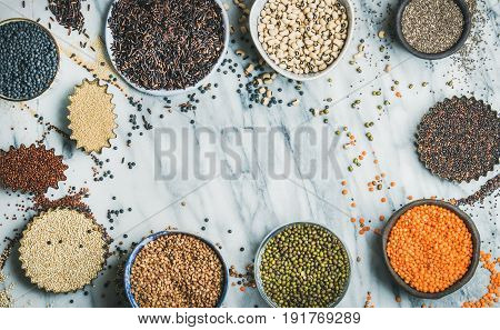 Various raw uncooked grains, beans, cereals in bowls and cups for healthy cooking over marble background, top view, copy space. Clean eating, dieting, healthy, detox, vegan, vegetarian food concept