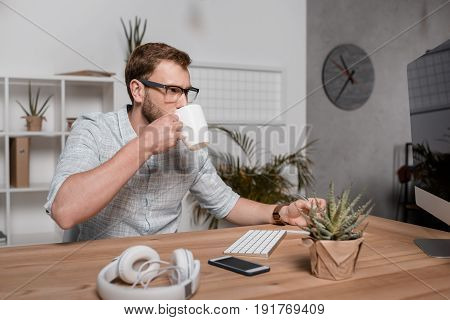 Focused Businessman Drinking Coffee While Looking At Computer Monitor And Sitting At Workplace