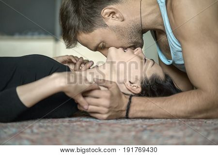 Kissing couple lies on the floor on the carpet. Guy wears a light sleeveless. Girl wears a black shirt. Their eyes are closed. Indoors. Closeup. Horizontal.