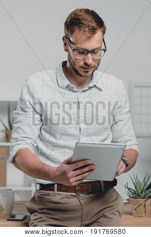 Focused Caucasian Businessman Using Digital Tablet And Leaning On Table In Modern Office