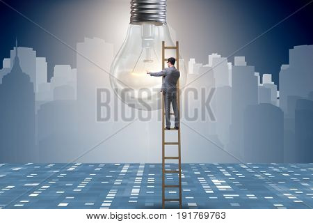 Businessman on ladder with light bulb