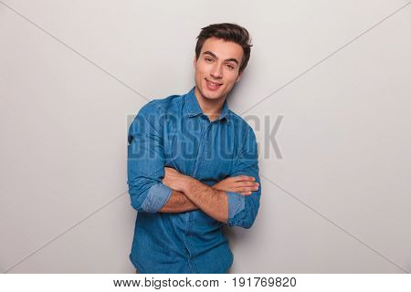smiling casual man with hands crossed standing against grey studio wall