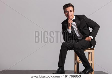 smiling seated man in tuxedo is thinking on grey background