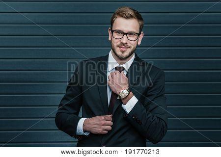 Smiling Businessman In Eyeglasses Tying Necktie And Looking At Camera