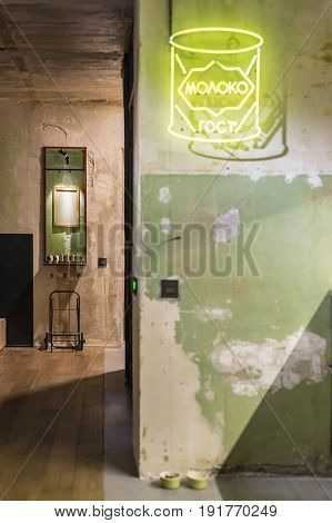 Glowing room in a loft style with shabby walls and a parquet on the floor. There is a luminous yellow signboard on the wall, mirror, switches and pet's green bowls on the floor. Vertical. Inscription translated as word of russian language - milk.