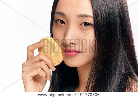 Woman with sponge, woman rubs her face with sponge on isolated background portrait.