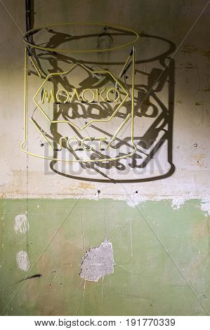 Yellow signboard is hanging on the shabby wall. It drops shadow on the wall. Closeup. Vertical. Inscription translated as word of russian language - milk.