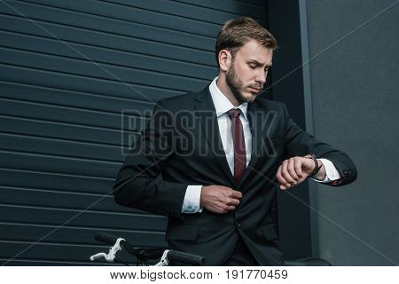 Stylish Young Businessman Sitting On Bicycle And Looking At Wristwatch