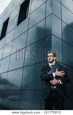 Stylish Handsome Businessman In Eyeglasses Hugging Briefcase And Looking Away