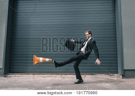 Excited businessman in eyeglasses holding briefcase and kicking traffic cone