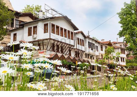 Melnik, Bulgaria - May 11, 2017: Traditional bulgarian houses of Revival period and flowers in Melnik town, Bulgaria