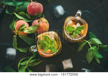 Summer refreshing cold peach ice tea with fresh mint in glass jars on metal tray background, top view